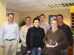 Pictured from left: Carl Woodland, COO Oasys Exhibitions, Craig Andrew, Key Account Manager Oasys Exhibitions, Sanet Delport, Project Manager Momentum McCann, Henry Jacobs, Oasys Exhibitions Design Manager, Wayne Parry, MD Momentum McCann holding the symbol of partnership between the two companies, and Kevin Hughes, COO Oasys Electrical.