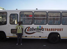 Founder of Zabeswa, Joseph Ntuli, standing proudly next to the Ubuhle bus transport