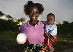 Priscilla and her son in Zambia with a solar light. These lights are bringing clean, safe, affordable lighting to homes for the first time. (Image: Patrick Bentley)