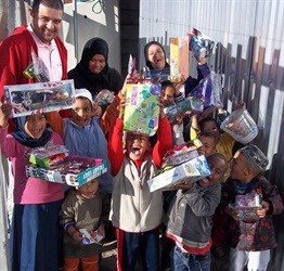 Fahim Docrat with overjoyed children after receiving their toys in Blikkiesdorp