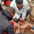 Ismail Rothman, Corobrik Building training coordinator shows CPUT learners how to lay paving.