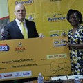 MTN's CEO Brian Gouldie handing over a dummy cheque of MTN Marathon proceeds worth shs.500 million to executive director of Kampala Capital City Authority (KCCA), Jenifer Musisi.