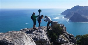 Behind the scenes: #TrekSouthAfrica project lead Andre Van Kets helps Devon Krantz load-up the 22kg Google Trekker backpack as Carte Blanche cameraman Greg Nelson captures the moment with Hout Bay in the background, June 2016. - Photo: Liz Fish