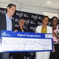 Tigo Tanzania Managing Director, Diego Gutierrez (right), hands over a dummy cheque to Nancy Sumari, (right, in white).