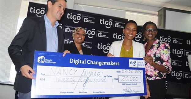 Tigo Tanzania Managing Director, Diego Gutierrez (right), hands over a dummy cheque to Nancy Sumari, (right, in white).