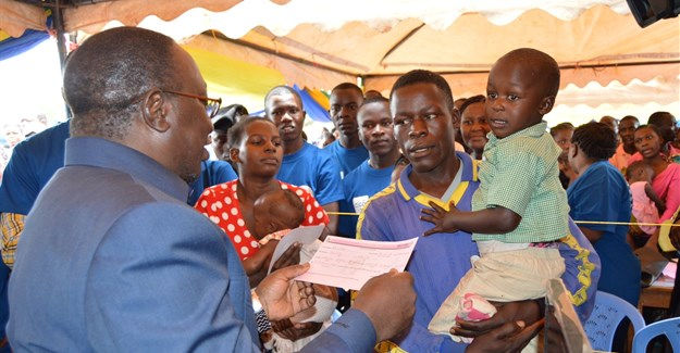 Minister for Constitutional Affairs, Dr Harrison Mwakyembe (L) presents a birth certificate to a parent during the launch of mobile birth registration campaign in Geita and Shinyanga Regions. Tigo Tanzania donated 1,200 mobile phones to support the exercise. Credit: Tigo.