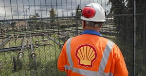 An employee at the Shell Agbada 2 flow station looks at the station from behind a gate in Port Harcourt on September 30, 2015.