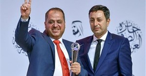 AFP photographer Jaafar Ashtiyeh gestures after receiving a top Arab prize for his coverage of the clashes in Kfar Qaddum at the 16th Arab Journalism Award (AJA) in Dubai's Madinat Jumeirah on May 2, 2017 |