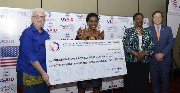 US Ambassador Deborah Malac, Power Africa coordinator Andrew Herscowitz, and Irene Muloni, minister of energy and mineral development, award CEO of CODE Uganda.