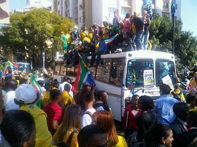 Bafana Bafana supporters climbing on a bus.